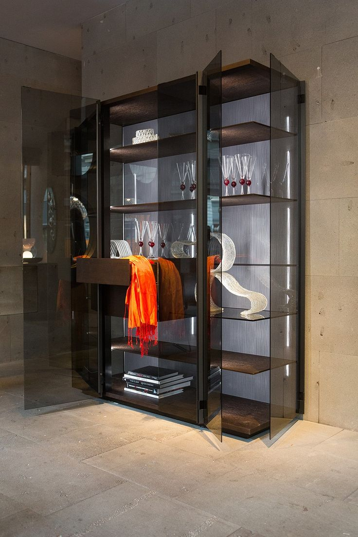 Display cabinet VELAQUADRA: display case with alluminium supporting profiles painted in cast iron colour and 3000K natural LED lighting. Doors in temperade fumè glass, shelves in tempered fumè glass. Base, top and back panel in coke oak.
