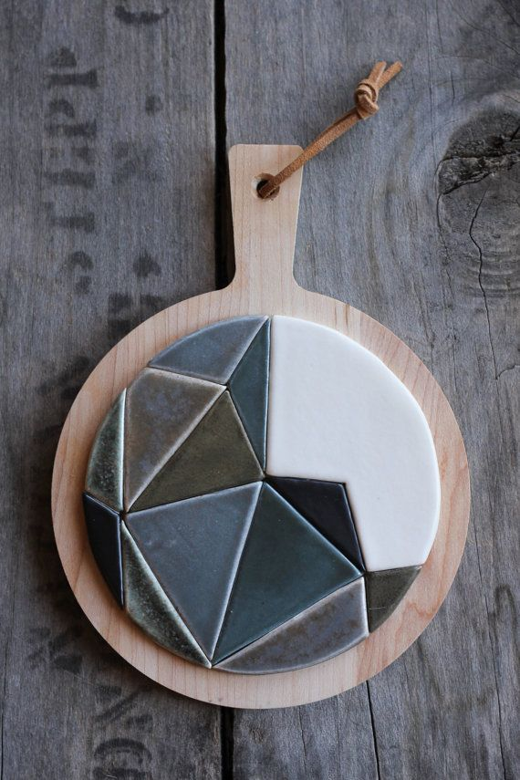A ceramic and wood trivet doubles as a hanging work of kitchen-friendly art.