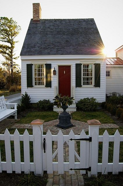 Colonial cottage by the sea ~ dream come true!  Love the fencing and the stone walkway too.  No fireplace required ~ unless it was electric with the faux brick on top for decoration.  Seems a bit wasteful though.