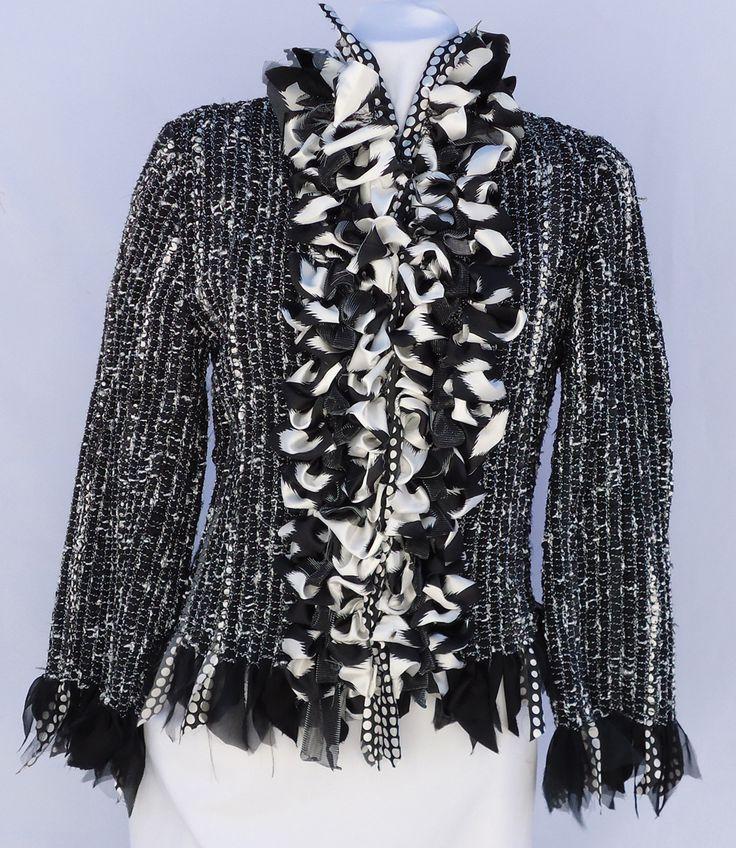 Vistosa composición de bullones en estampas en tonos blanco, negro y plateado decoran el peto de esta chaqueta. Flecos de diversos géneros rematan su contorno. Medidas: talla 44  Técnica: telar manual.  Hilados: algodón, seda, lurex. Géneros: seda, gasa, satén.