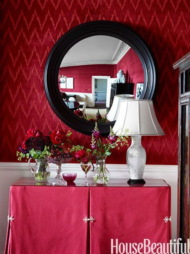 A convex mirror from John Rosselli Antiques expands the boundaries of the dining room.