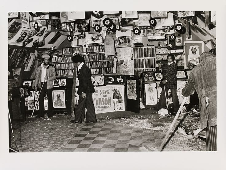 Neil Kenlock, 'Untitled [Desmond's (standing with broom on left) Hip City records shop in Brixton South, London, damaged by National Front  members]', 1974. Museum no. E.219-2012. © Neil Kenlock/ Victoria and Albert Museum, London. Supported by the National Lottery through the Heritage Lottery Fund.