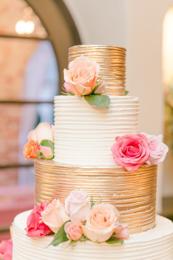Gold and white rose topped wedding cake.