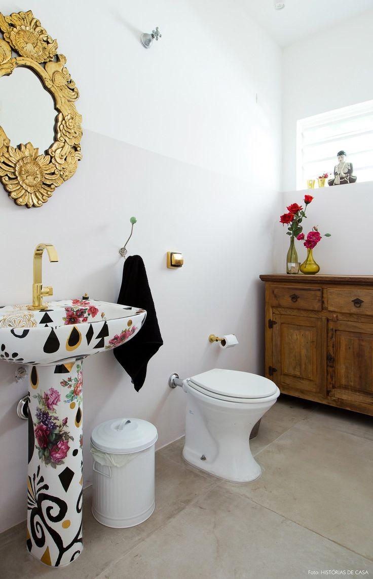 Banheiro tem piso de cimento queimado e cuba estampada pela artista Calu Fontes.
