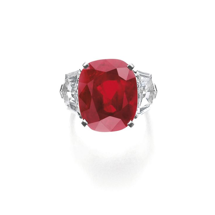 Superb and extremely rare ruby and diamond ring, Cartier Set with a cushion-shaped ruby weighing 25.59 carats, between shield-shaped diamonds weighing 2.47 and 2.70 carats, signed Cartier, numbered, French assay and maker's marks, size 54, case signed Cartier.