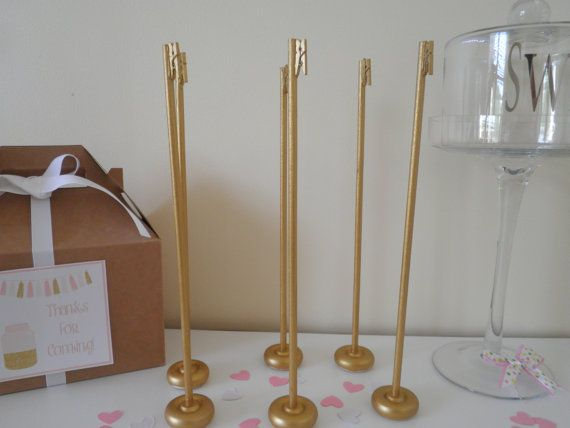 This is an AWFUL photo, but these are cute: 12 handmade gold table number holders for $40 (we can ask her to do a custom order for however many tables you have). Could also be a cute stand for a small guest book sign, if needed