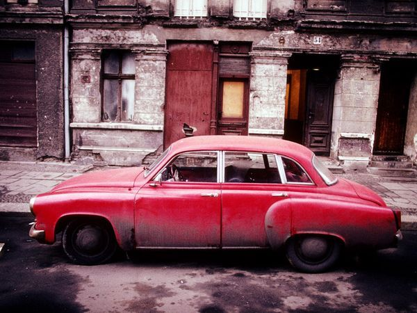 A red car sits on a dirty and deserted side street in communist East Berlin. East and West Germany were reunited in 1990 after 45 years of separation following the end of World War II.  Photograph by Ed Kashi