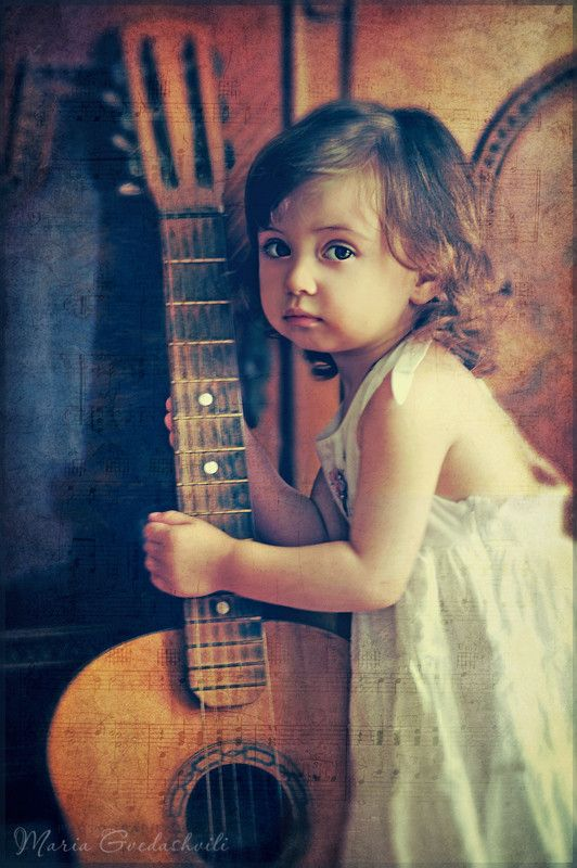 Little girl with guitar and texture music paper.
