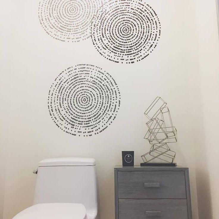 A stenciled bathroom accent wall using the resonance wall art stencil from cutting edge stencils