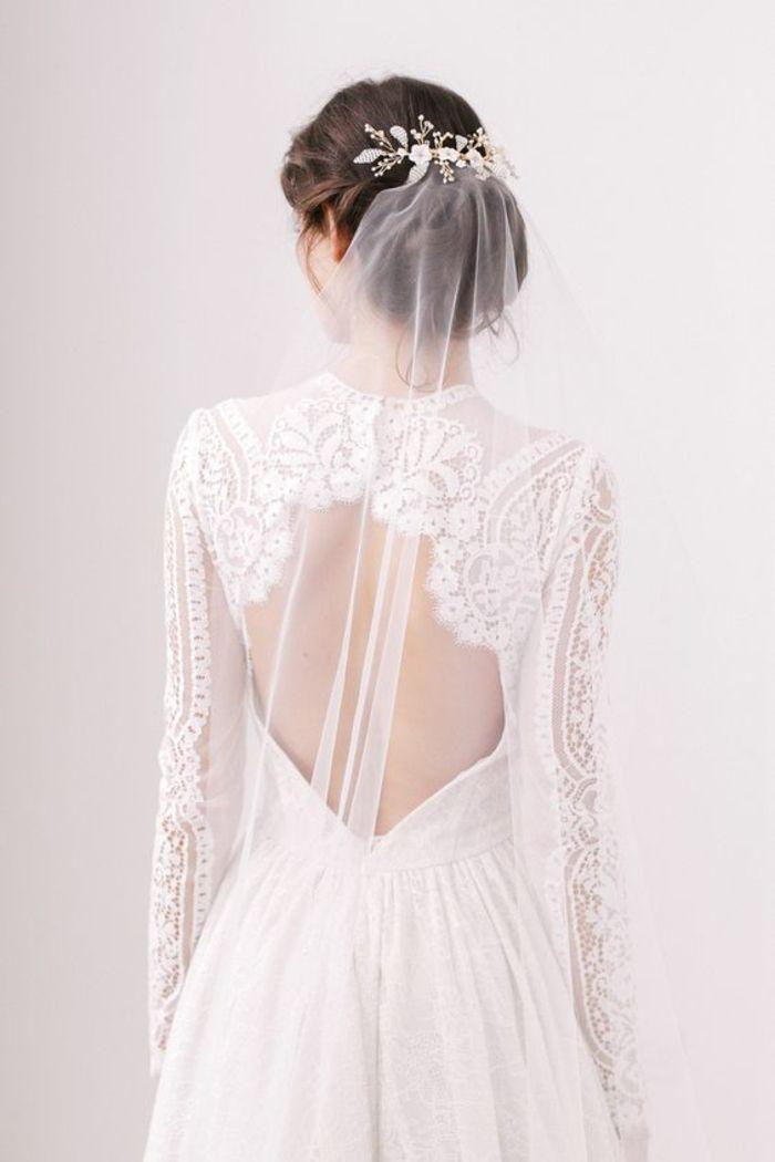 une robe de mariée à manches longues en dentelle, un voile mariée fixé avec un peigne