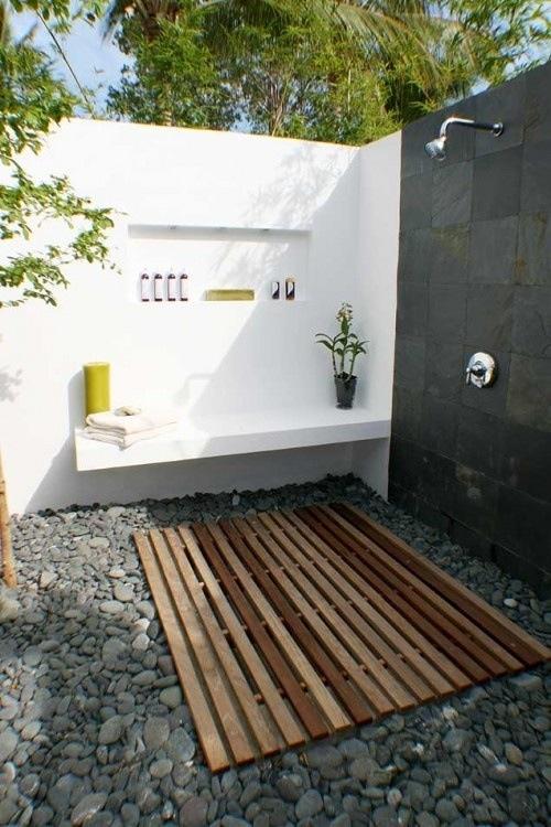 An outdoor bathroom with cedar floor and copper shower head. Pure luxury!