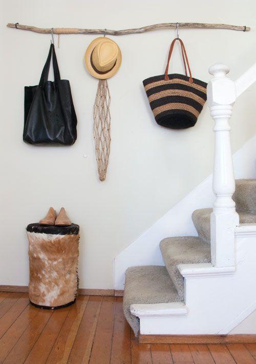 Une vieille branche au mur, quelques crochets et voilà un endroit où suspendre chapeaux et sacs. (Design Sponge)