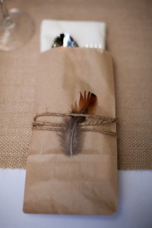 Rustic dinnerware setting.Small Paper bag, twine and a feather.