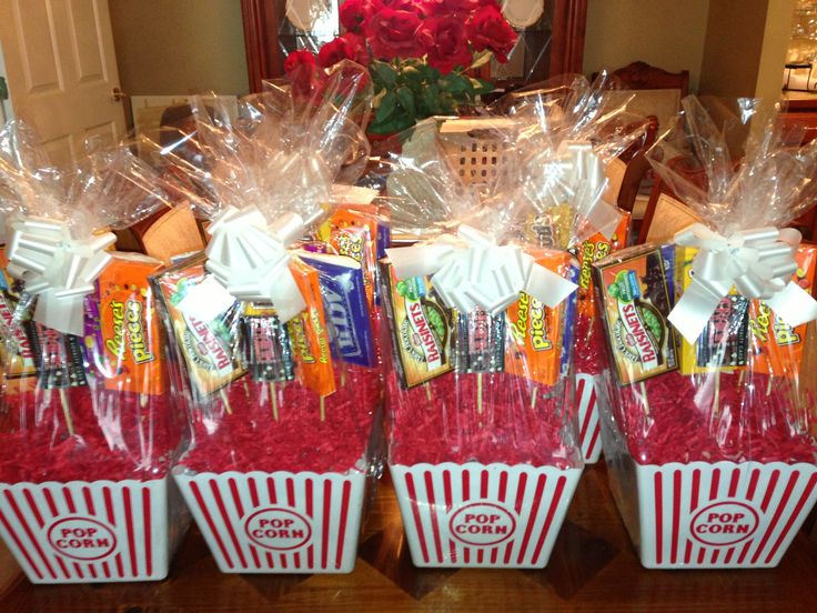 Movie gift baskets. Each contains a $10 movie theatre gift card, 4 Jumbo boxes of candy, 2 microwaveable popcorn & a popcorn bucket. I hot glued items onto skewer sticks & used styrofoam, white tissue paper & decorative rocks in the bottom of the popcorn container to help secure the top heavy candy boxes etc. I then used the shrink wrap bags & decorative filler from the local Dollar Tree that come with bows to finish them. Each basket cost approx $20.