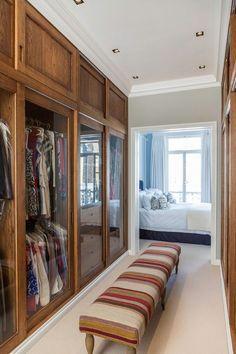 Chique e funcional: closet com luz natural, portas em madeira e vidro