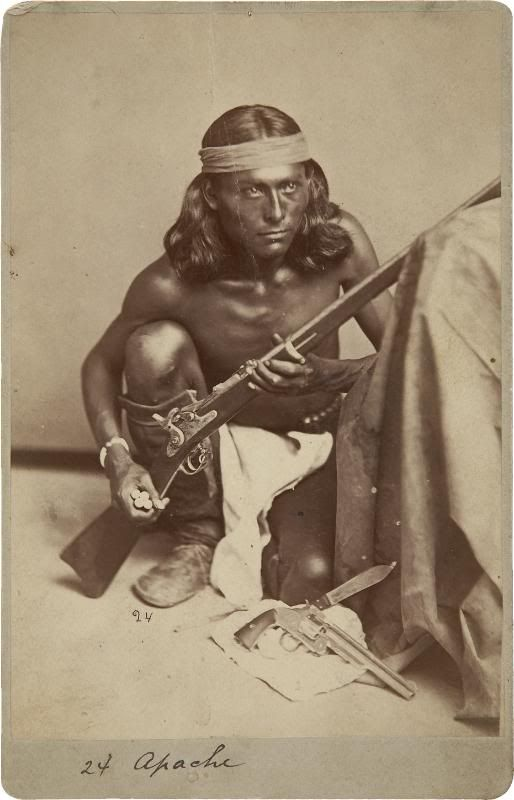 Apache Scout Nantaje, Awarded the Congressional Medal of Honor for Action Against Apaches on 12 April 1875. Nantaje holding a M1870 .50-70 rifle with cartridges in his hand. A Smith & Wesson 1st Model American and Bowie knife are on the floor in front of him.