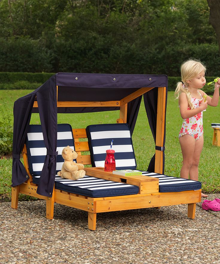 Your little one can lounge in style courtesy of this double chaise chair, boasting a canopy for cozy shade and a center cup holder to hold your little pal's refreshments. This piece's durable wood structure holds strong for all those days of outside lounging. Includes chair, cushions and canopy34'' W x 35'' H x 36.5'' DSanmu woodRecommended for ages 2 to 4 yearsImported