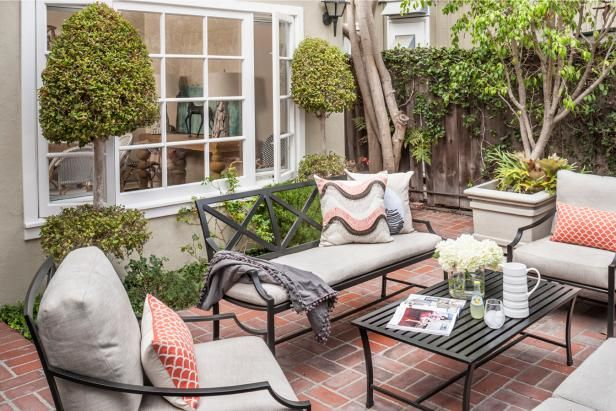Black Iron Patio Furniture With Neutral Cushions and Fish Scale Throw Pillows on Brick Back Patio