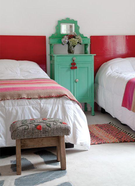 Dormitorio rústico con camas de respaldo rojo y mesa de luz compartida verde, más banquito como pie de cama en una casa de campo. Foto: Magalí Saberian