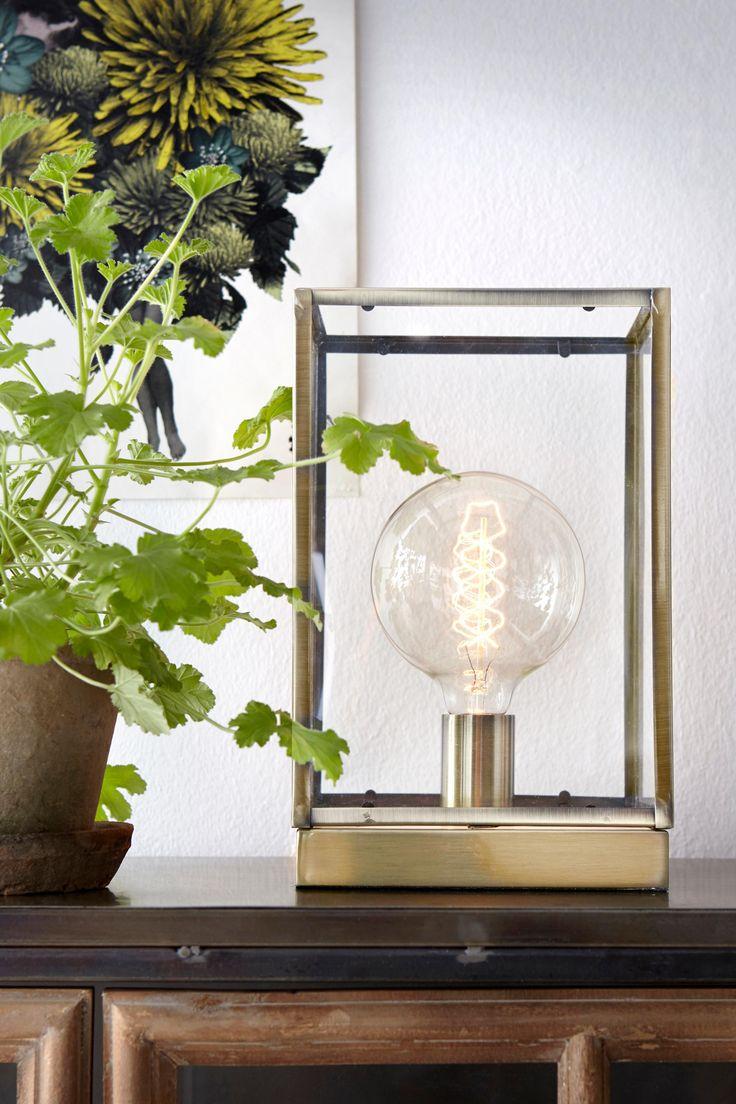 Dekorativ och stilfull bordslampa i en glasbox med kanter och botten i metall. Stl 20x20 cm. Höjd 32 cm. Textilkabel med strömbrytare, längd 210 cm. Stor sockel E27. Max 60W. Väggkontakt. Ljuskälla ingår ej. Olika typer av glödlampor förändrar stilen hos din lampa. Prova dig gärna fram till ditt eget uttryck!