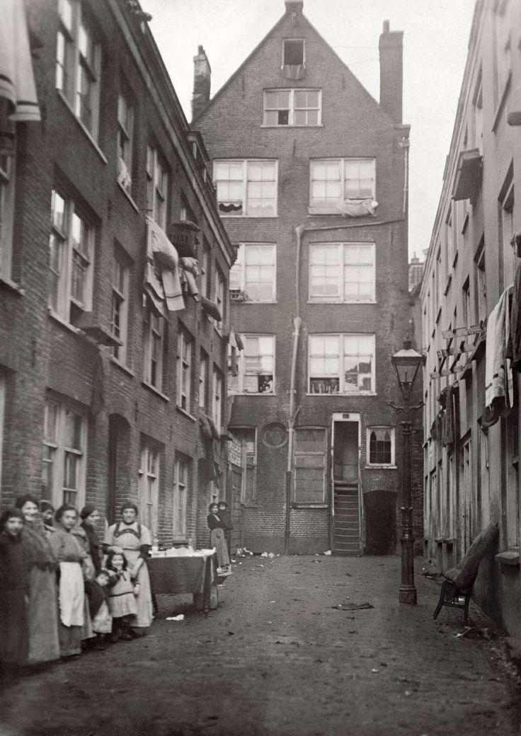Sloppen in de Jodenbuurt met een groepje vrouwen en kinderen. De huizen zouden al snel onbewoonbaar verklaard worden. Amsterdam, Nederland, 1916.