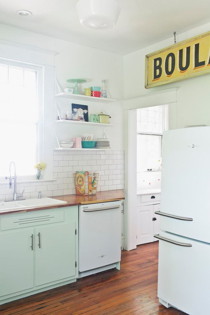 Mint kitchen cabinets with GE Artistry Series appliances, butcher block counters, open shelving