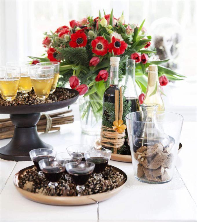 Den ståtliga adventsbuketten som består av röda tulpaner och anemoner, prärieklocka och limonium har Linnea gjort. Dekorera en flaska glögg med granris, kanelstänger och en vacker orkidé. Här har Linnea lindat färgade yllesnören runtomkring. Bra tips på present att ge bort! Tallkottarna på fatet är en enkel dekoration som lyfter dukningen. Glögg och alkoholfri kanelsmutt från Västergården är dukade i vackra glas.