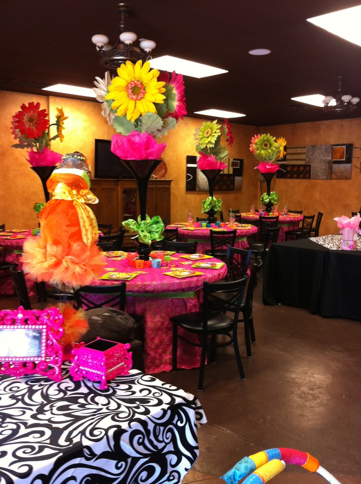 Love all the colors here! Maybe hang flowers or poms from the ceiling fans?!