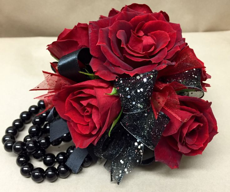 a wrist corsage featuring red tea roses with black and red ribbon accents – 36.95 - http://www.leighflorist.com #prom #promflowers #leighflorist