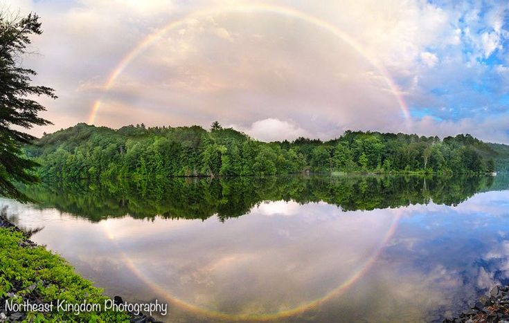 THE FULL CIRCLE RAINBOW  Photograph by JENNIFER HANNUX/Northeast Kingdom Photography Website   Facebook   Prints available  In this stunning capture by Jennifer Hannux of Northeast Kingdom Photography, we see a rainbow perfectly reflected in the river below, creating a beautifully framed full circle rainbow. The image is a stitched panorama taken with…