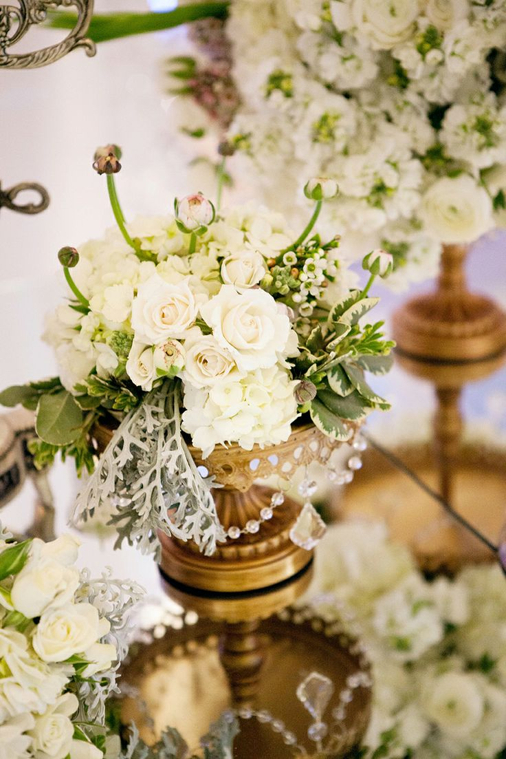 Tablescapes | Floral Works & Events | roses, pitt, and dusty miller in gold vessels on a gold mirror top table.