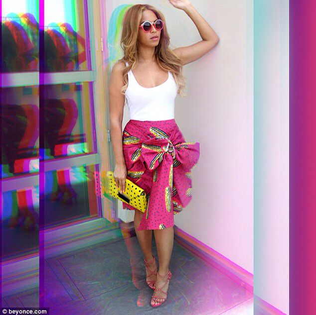Beyonce wore a fitted white tank top, which featured a plunging neckline that showed a hint of the singer's ample cleavage. She wore that tucked into a pink skirt with a large bow on the front, that was decorated with a bright yellow corn pattern. The Crazy In Love singer coordinated her look, by sporting a pair of studded, strappy hot pink heels, which went well with her summery skirt.