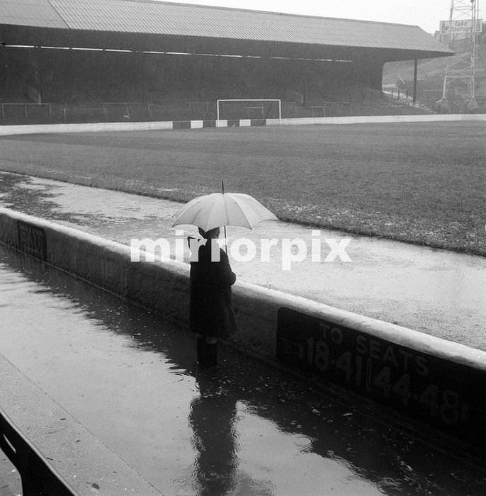 A spectator with an umbrella looks at flooded football ground The Valley, home of Charlton Athletic Football Club November 1961