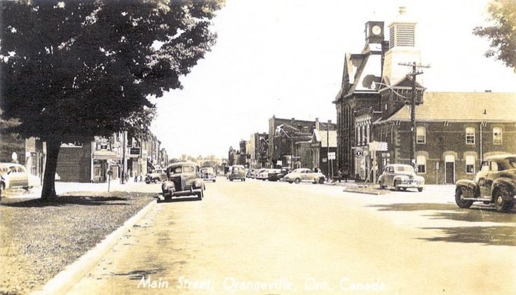 This postcard shows Broadway from John St. looking East. Many of the buildings pictured here are still standing, including the firehall (no longer in use) on the right.