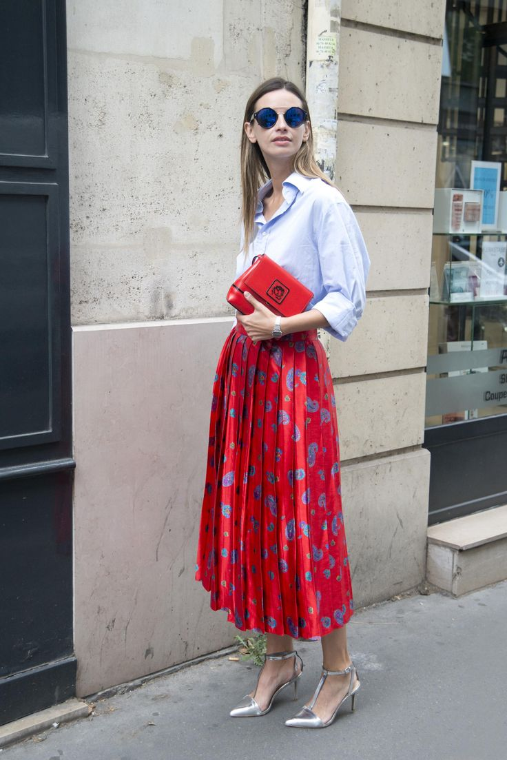 Street style star Clara Racz wearing a baggy button-down shirt styled with a gorgeous red floral midi dress and matching bag