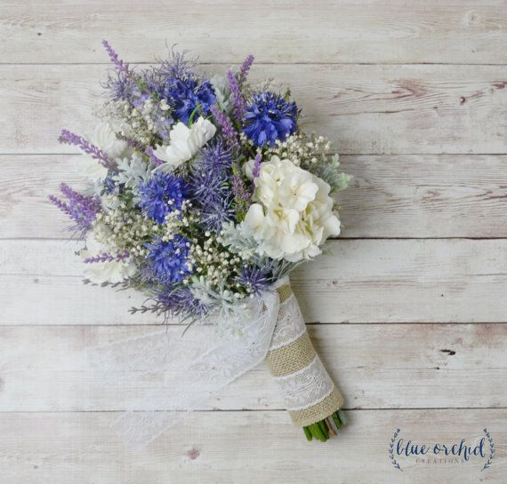 Wildflower bridal bouquet in shades of purple and blue. This boho bouquet is filled with lavender, light purple wildflowers, blue cornflowers, and dried babys breath. The silk wildflowers are all mixed together to create a rustic, woodland wedding bouquet with a ton of texture. This bouquet travels well and would be perfect for a destination wedding! Shown wrapped in burlap with a cream lace overlay. The bridal bouquet pictured is a small bridal bouquet, which is about 8-10 wide and 12 tall…
