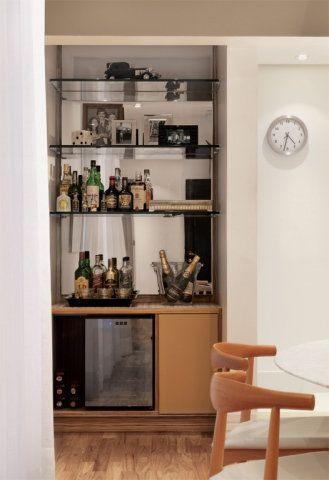 """Despensa vira adega charmosa. Esta área, de 1,20 x 1 m, antes destinada à despensa da cozinha, se transformou num charmoso cantinho para abrigar a adega e o bar que os moradores tanto desejavam. Aberto para a sala de jantar, o espaço ganhou um espelho bronze no fundo e três prateleiras de vidro de 1,20 m x 20 cm de profundidade. """"Uma lâmpada dicroica ilumina o móvel e produz um interessante jogo de reflexos"""", conta a arquiteta Ana Rita Souza e Silva. Na parte inferior, o tampo é revestido…"""