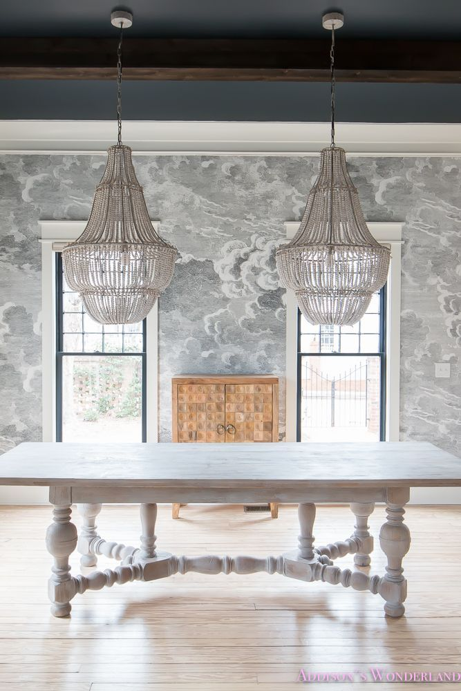 A whimsical dining room completed with a dramatic cloud wallpaper and beaded chandeliers. Featuring a wooden cabinet and accessories from HomeGoods. Sponsored by HomeGoods.
