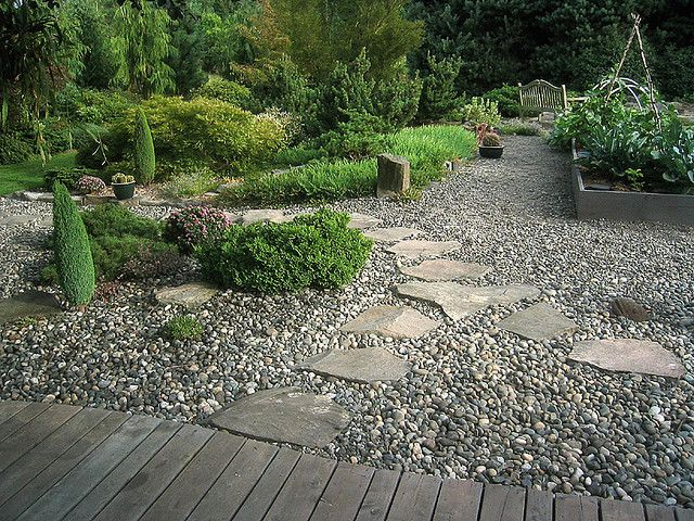 gravel patio -- love to do something similar under the deck, with flagstone path and plants around the edges -- would so help with drainage, too...