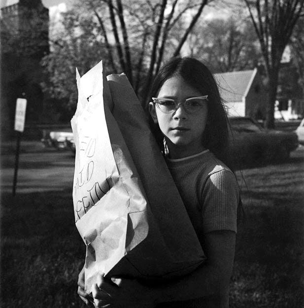 A girl with sixties-style glasses and apprehensive face carrying a big paper bag with writing, looking straight at the camera. See a Stunning New Set of Vivian Maier Photos from Eye to Eye | Chicago magazine | July 2014