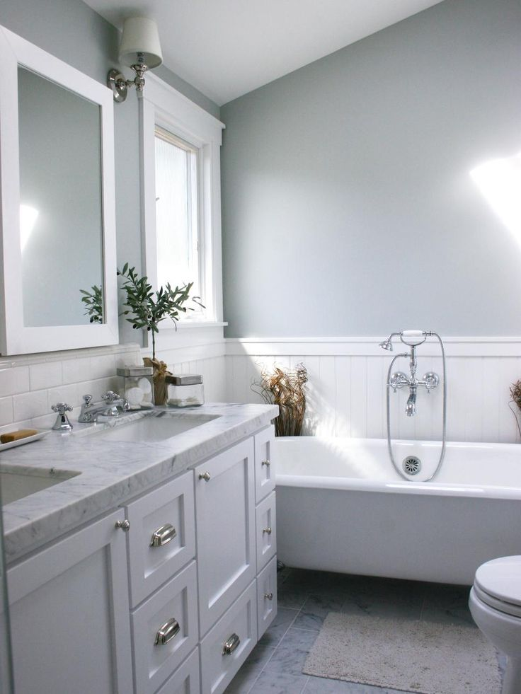 A white bathtub, backsplash tile, mirror and window frame contrast with the gray walls and gray marble bathroom vanity in this small bathroom that has a marble tile floor.
