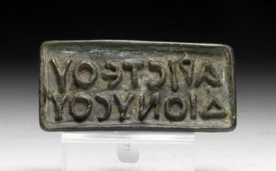 Bronze rectangular bread stamp, late Roman, early Byzatine period, 4th-7th century A.D.   A bronze rectangular bread stamp with ring handle, recessed within the frame is a two line retrograde Greek inscription identifying the owner as Aristeos Dionysos, 8.2 cm long. Private collection