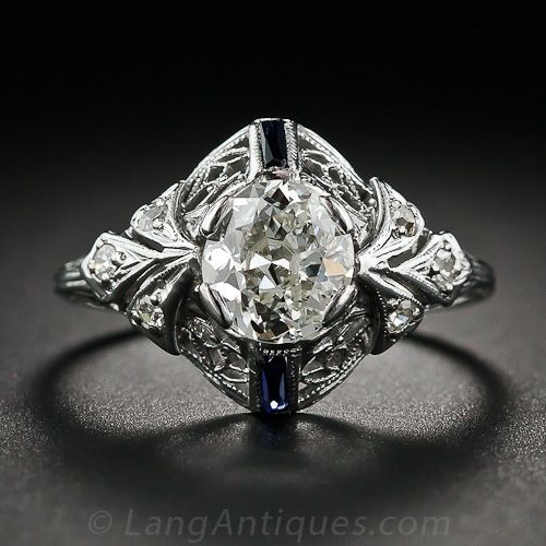 An exquisite Edwardian setting, finely crafted in lacy 18 karat white gold and exhibiting a touch of Art Deco flair, presents a rather unusual, bright and shining, one carat center stone. The beautiful diamond is not quite an antique cushion-cut, and not quite a European-cut, but an old mine-cut roundish-oval. The gracefully domed mounting is imbued with delicate open scroll work leading to diamond-set trefoil shoulders and accented with a pair of royal blue baguette sapphires.