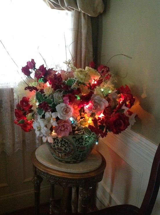 A silk flower arrangement with a string of white lights for Dining room flower arrangements