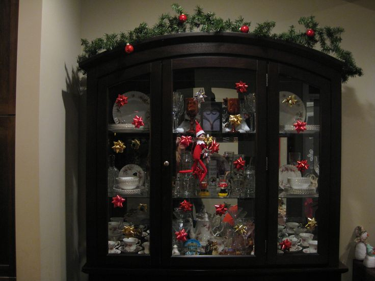 """December 19, 2014 ~ Sparky decorated our china cabinet with bows and decided to """"mountain climb""""."""