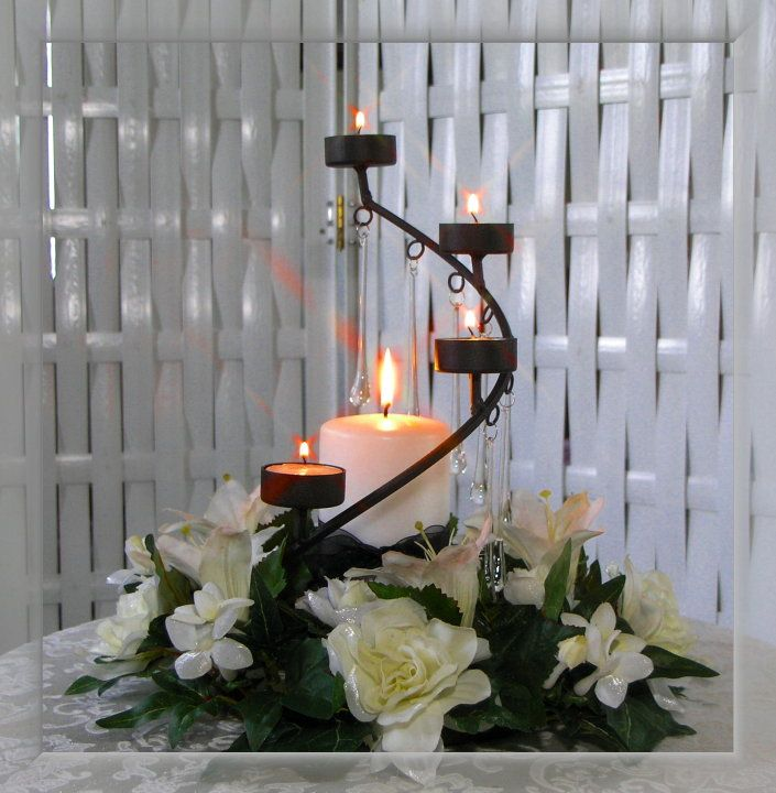 Imagen: centro de mesa con velas y flores blancas.