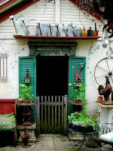 Potting shed with watering can collection plus more garden art.  love the gate but where is the door?