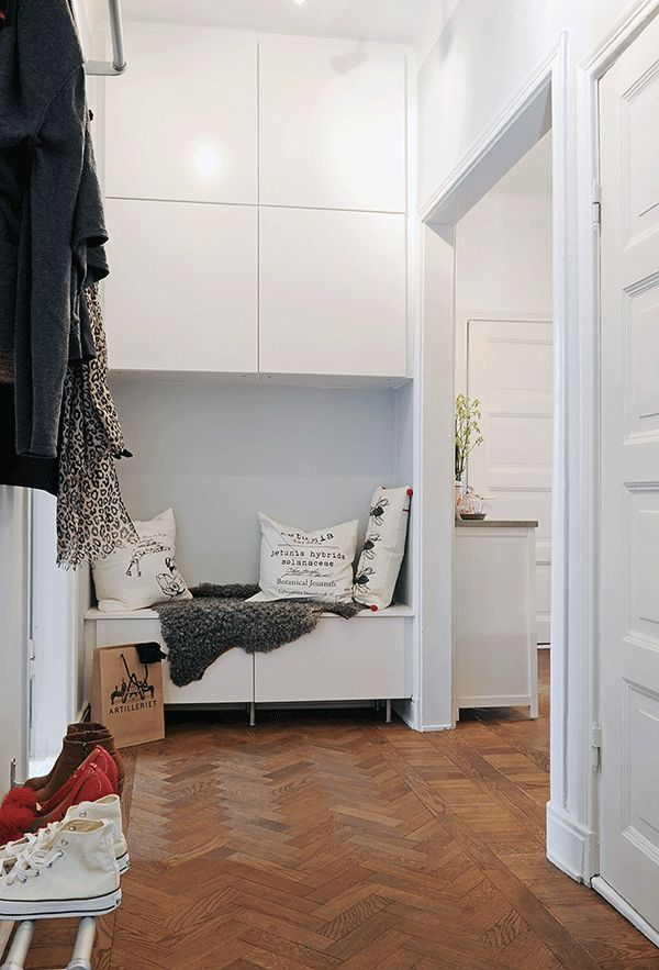 I like this split storage look for a hallway - less loss of perceived space than floor-ceiling cupboards.  However, in our home, the bit occupied by tasteful throw & cushions would be gym bags....