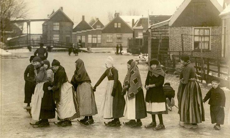 Een rij meisjes schaatst dik ingepakt tegen de kou. Schaatsen in Volendam. 1919. #NoordHolland #Volendam