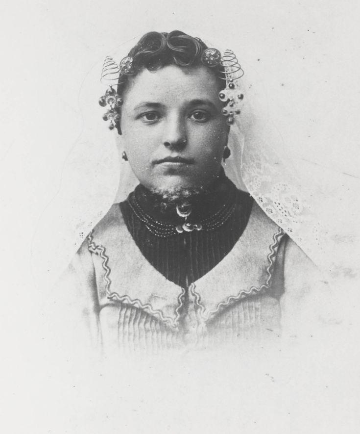 Vrouw uit Kortgene in Noord-Bevelandse dracht. ca 1900 Ze draagt de lange muts. Aan de krullen van het oorijzer hangen 'steenbellen'. Zij heeft het haar in zogenaamde 'draaitjes' gelegd. Vanaf de middenscheiding een soort liggende S-vorm. Dit is een typerende, doch niet algemeen voorkomende haardracht voor Noord-Beveland. #NoordBeveland #Zeeland